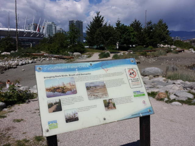 A Vancouver City Parks Board information sign in front of the entry to what some call Habitat Island with trees and BC Place Stadium in the background.