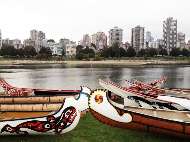Beautiful canoes on the edge of False Creek are depicted in the foreground, displaying indigenous art. The canoe in the bottom left corner displays a whale. In the background is part of Vancouver's skyline with many grey skyscrapers and trees.